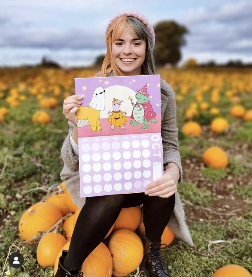 Girl sat on a pile of pumpkins in a pumpkin field holding a calendar opened to the October page.