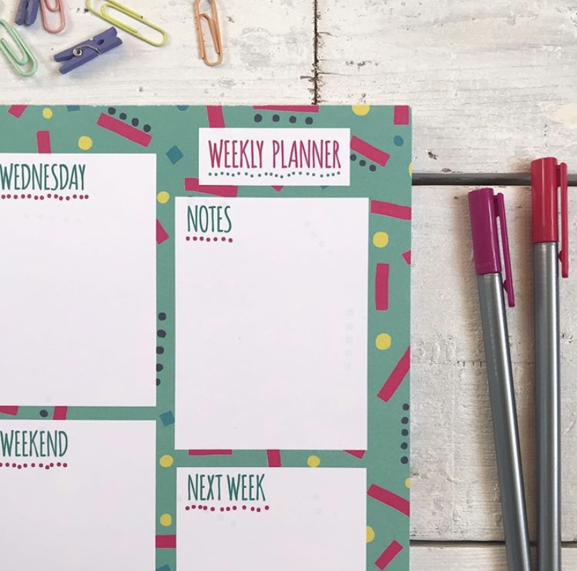 Weekly planner pad close up surrounded by pens and paperclips.