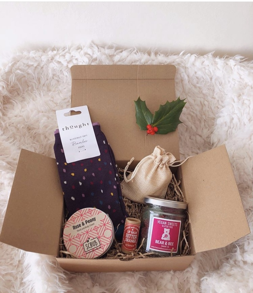 Gift box laying open on a fluffy rug, packed full of things.