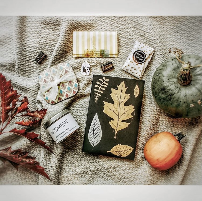 Lots of stocking filler type gifts laid out on a blanket, surrounded by foliage and pumpkins.