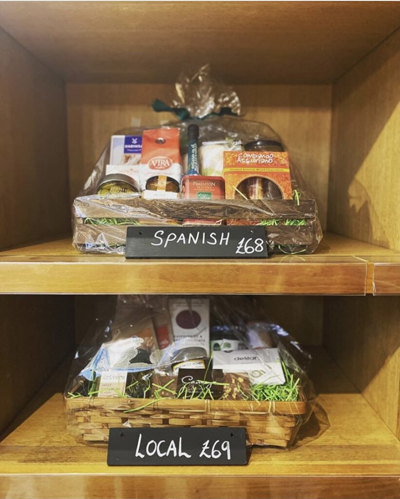 Two food hampers, beautifully wrapped on a shelf with price and name labels.
