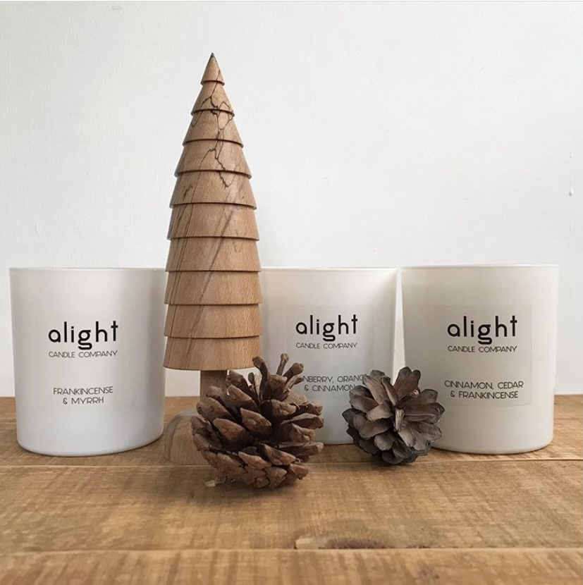 A set of three votive cabndles surrounded by wooden Christmas decorations.