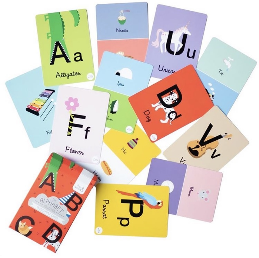 Alphabet flashcards scattered.